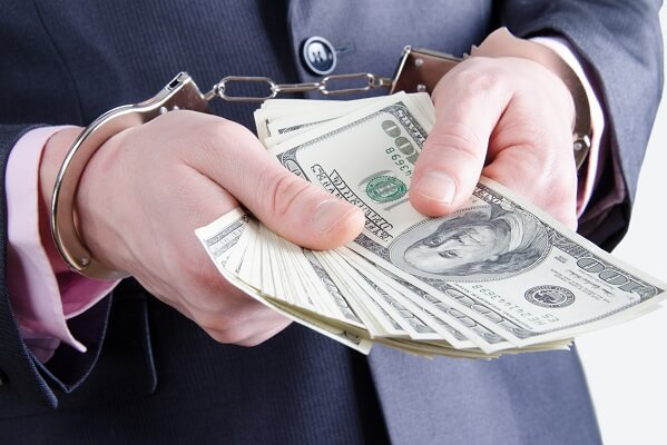 man in handcuffs holding bribery money
