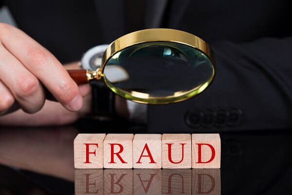 using magnifying glass to investigate fraud