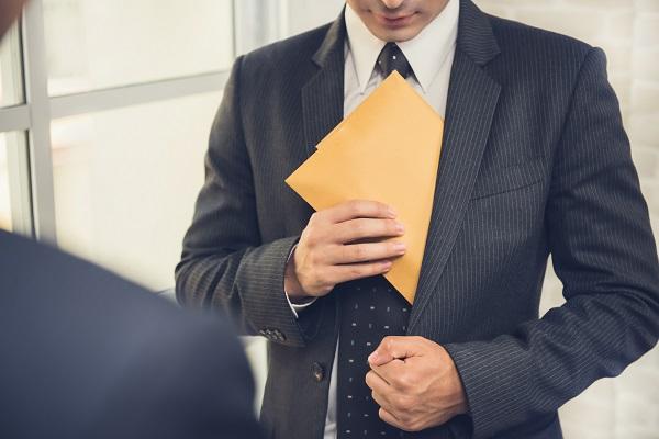 Businessman putting the envelope into his suit pocket - corruption and embezzlement concepts