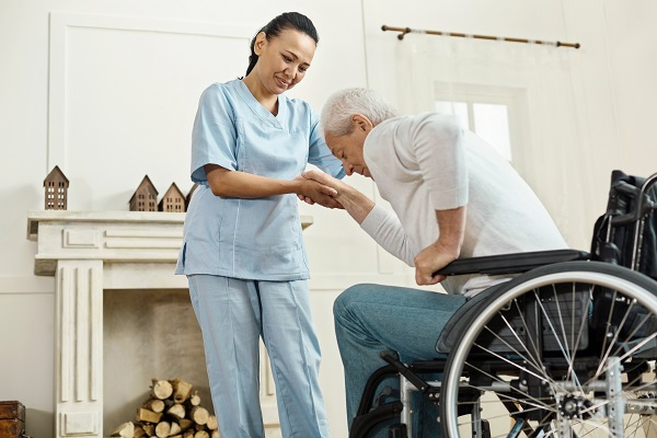 Medical assistance. Pleasant good looking senior man holding caregivers hand and getting up from the wheelchair while staying at the nursing home