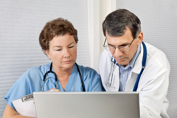 Doctor And Nurse Talking and Working at Laptop Computer In Office